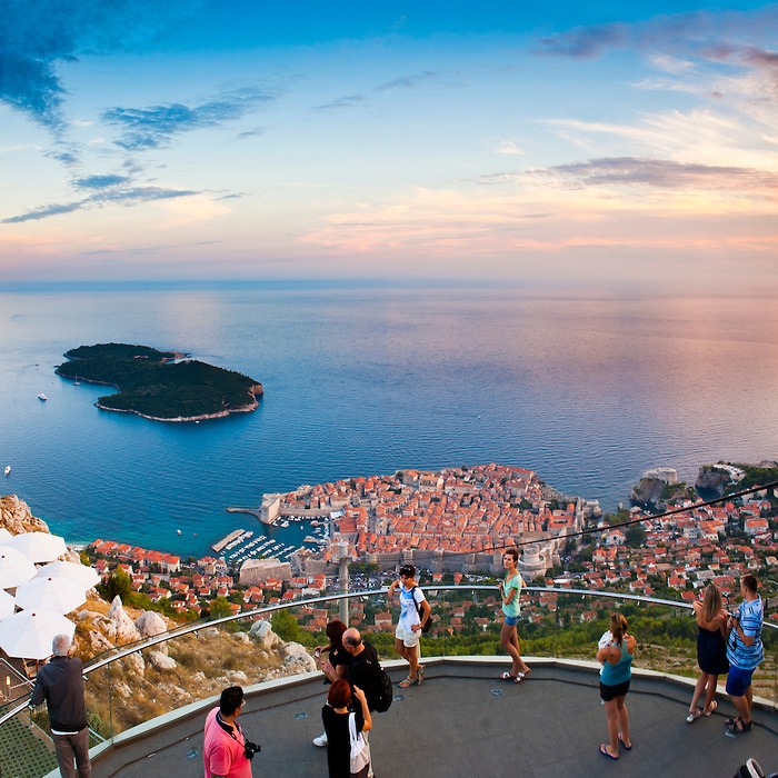 Tourist at the top of Dubrovnik cable car at sunset enjoying the views over Dubrovnik Old Town and Lokrum Island, Dalmatian Coast, Croatia. This photo shows tourists enjoying views from the top of Dubrovnik cable car. The cable car provides beautiful views over Dubrovnik Old Town and Lokrum Island, especially at sunset.